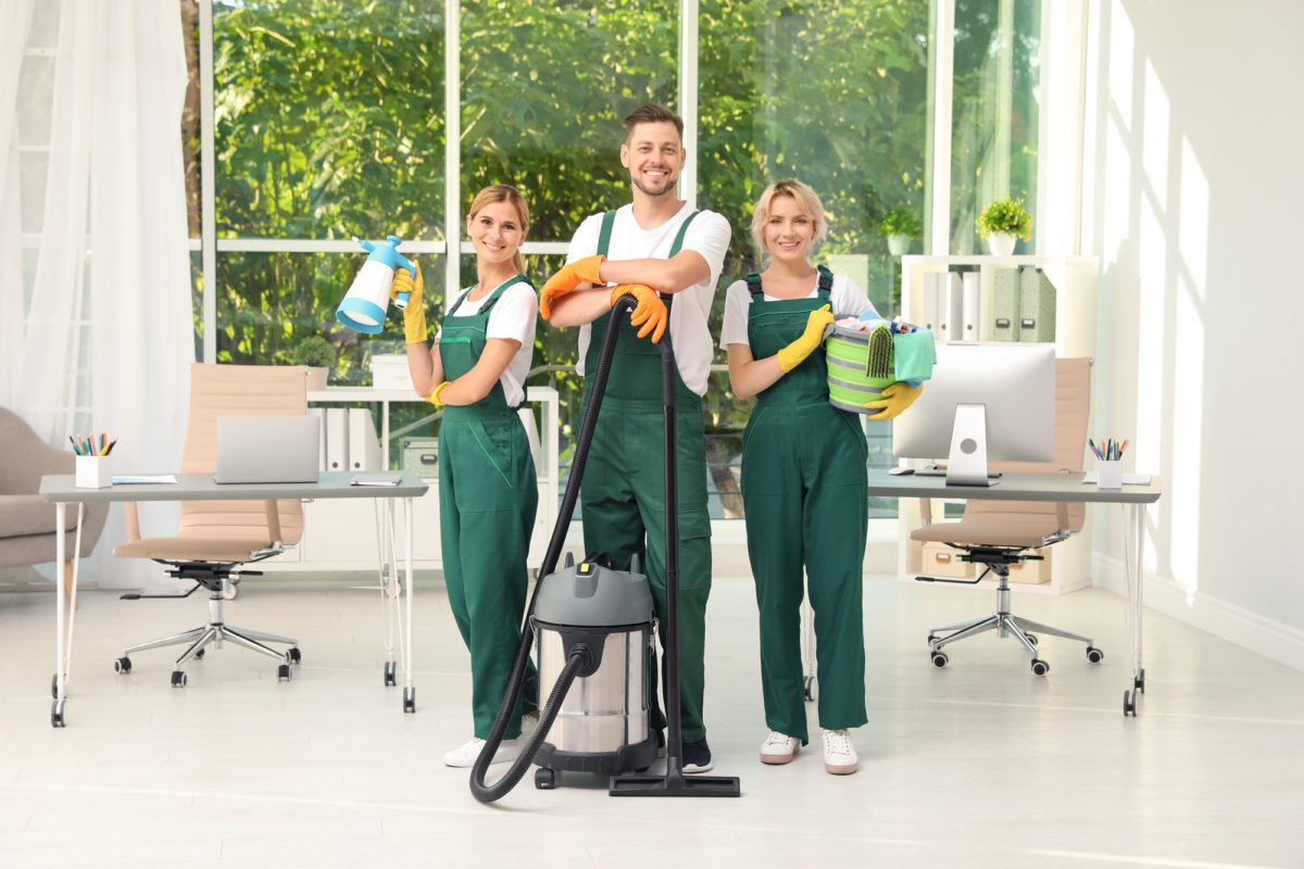 people smiling with cleaning supplies